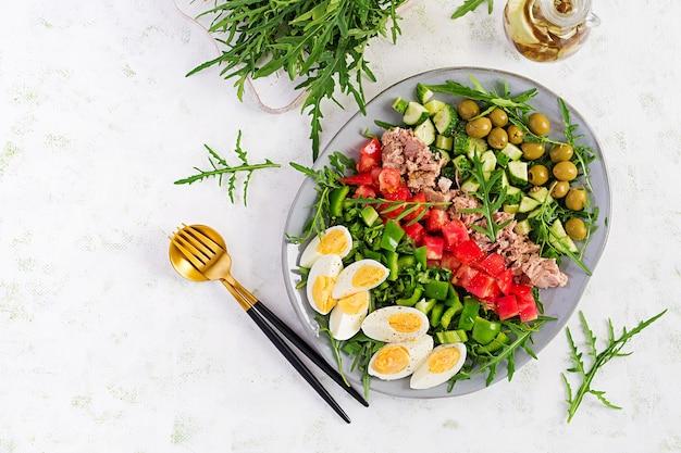 Cibo salutare. insalata di tonno con uova, cetrioli, pomodori, olive e rucola. cucina francese. vista dall'alto, copia spazio, laici piatta