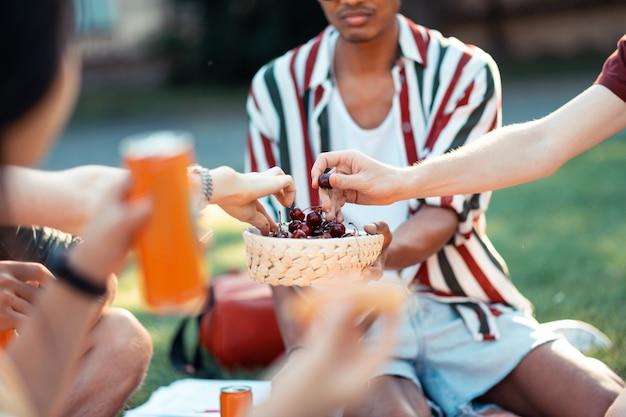 Cibo salutare. amici dell'università seduti insieme sull'erba a mangiare le ciliegie dal cesto durante il picnic estivo.