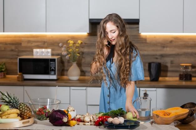 Cibo sano - insalata di verdure. dieta. concetto dieta. giovane donna riccia che prepara insalata di verdure nella sua cucina, che parla sul telefono cellulare e che sorride mentre. concetto di stile di vita sano.