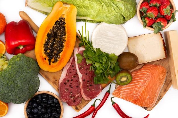 Cibo sano sul tavolo bianco, frutta, verdura, carne e pesce, vista dall'alto