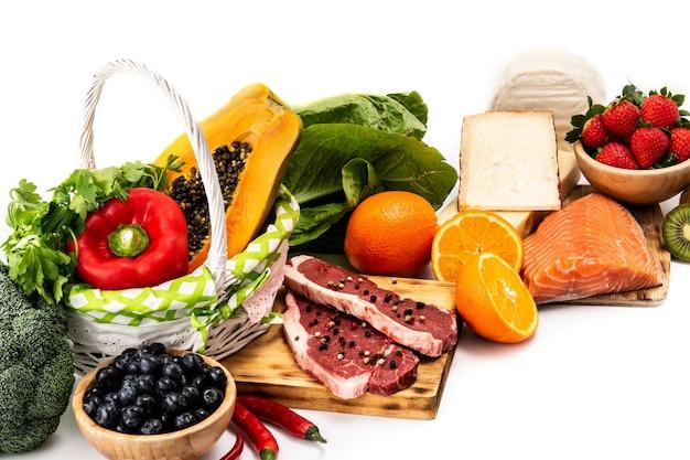 Cibo sano su tavola bianca, frutta, verdura, carne e pesce