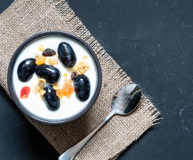 Cibo sano, yogurt con cereali nella ciotola vista dall'alto sul buio isolato