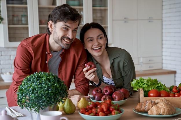 Cibo sano giovane bella famiglia coppia marito e moglie in piedi nella cucina moderna a casa