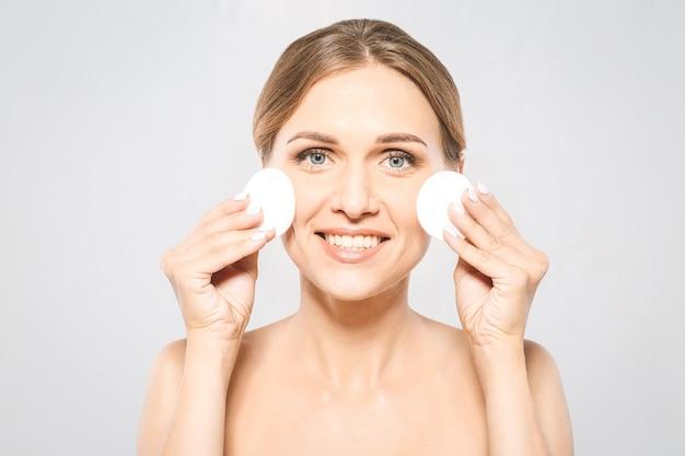 Ragazza fresca in buona salute, rimuovere il trucco dal viso con un batuffolo di cotone. donna di bellezza che pulisce il suo fronte con un tampone di cotone isolato su sfondo bianco isolato. la cura della pelle e il concetto di bellezza.