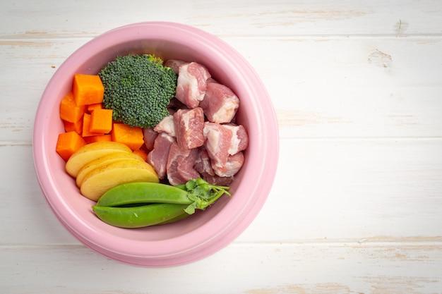 Ingredienti alimentari freschi sani per animali domestici su superficie di legno bianca