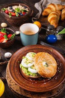 Un sano bagel appena sfornato ripieno di uova bollite, avocado ed erba cipollina. cibo per la colazione