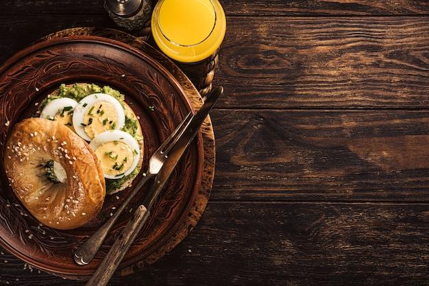 Un sano bagel appena sfornato riempito con uova bollite, avocado ed erba cipollina