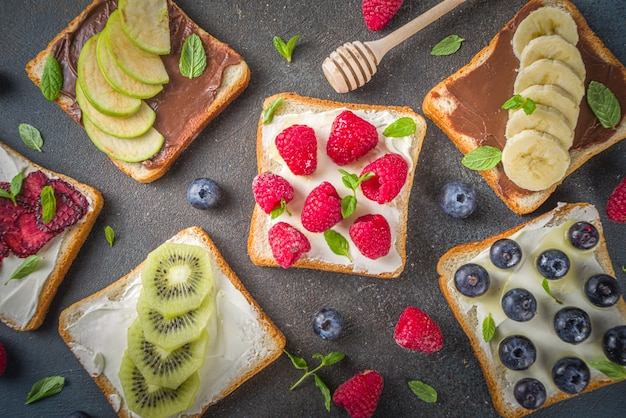 Panini sani di frutta e bacche. pane tostato dieta gustosa con crema di formaggio e banana, mela, lampone, mirtillo, fragola, su sfondo blu scuro vista dall'alto lo spazio della copia