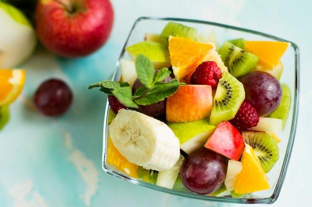 Una sana insalata di frutta a base di fette di banana, kiwi, arancia e uva in vetro. vista dall'alto.