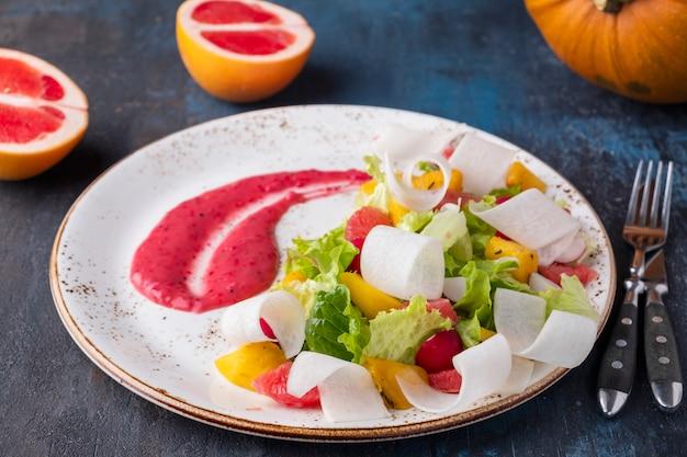 Insalata di frutta sana con pompelmo e zucca, lattuga e salsa rossa