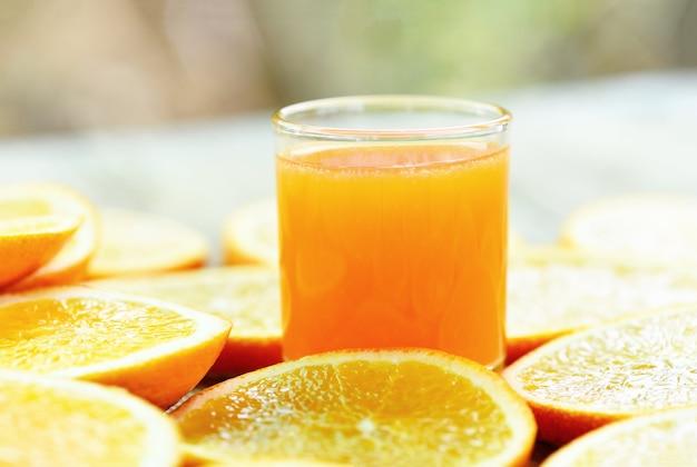 Frutti sani e fetta d'arancia, succo d'arancia fresco nel bicchiere con frutta arancione su legno