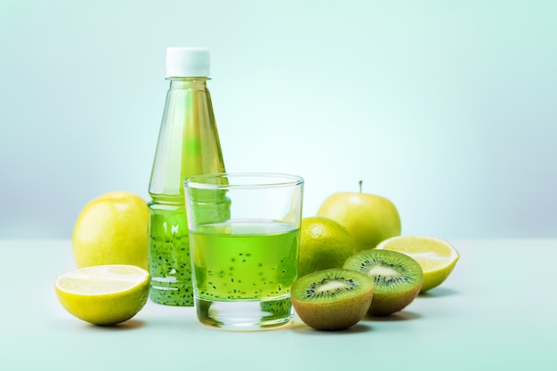 Succo di disintossicazione verde sano con frutta su sfondo color menta