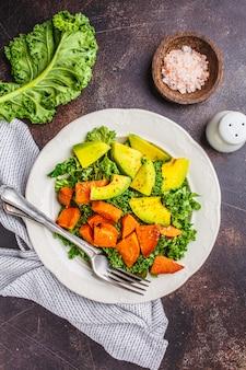 Insalata di cavolo verde sano con avocado e patate dolci al forno.