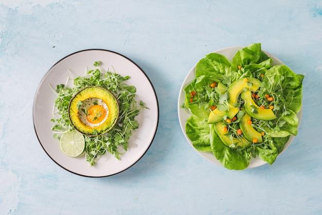 Insalata verde salutare di avocado, cetriolo, uva, prezzemolo e lattuga con condimento all'olio d'oliva, aceto balsamico e senape in grani.