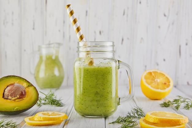 Frullato verde sano, alimentazione sana e nutrizione, stile di vita, vegano, alcalino, concetto vegetariano. frullato verde con ingredienti biologici, verdure su un tavolo di legno bianco