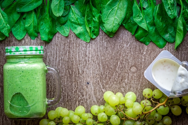 Frullato verde sano con spinaci in una tazza contro su fondo di legno