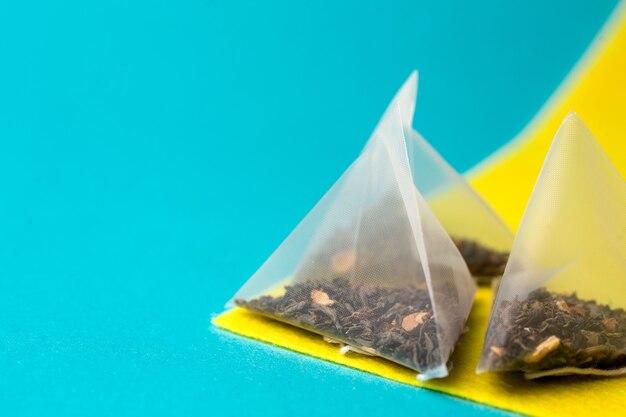 Tè verde sano in un sacchetto piramidale su sfondo blu e giallo