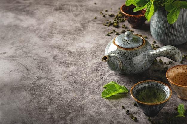 Tè verde, cerimonia del tè, teiera e tazze sani per una bevanda, spazio della copia, fondo grigio