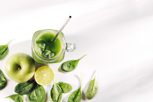Succo di verdura verde sano con spinaci e frutta e verdura verdi sul tavolo bianco.