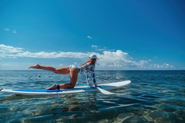 Donna sana e felice in forma in bikini che si rilassa su una tavola da surf sup che galleggia sul limpido mare turchese