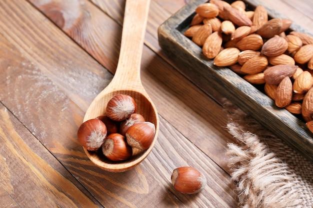 Nocciola sana e noci di mandorle su superficie di legno