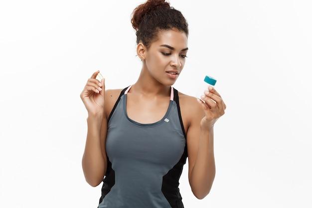 Concetto sano e sanitario - ritratto di bella bottiglia di bottiglia supplementare sportiva africano americano. isolato su sfondo bianco studio.