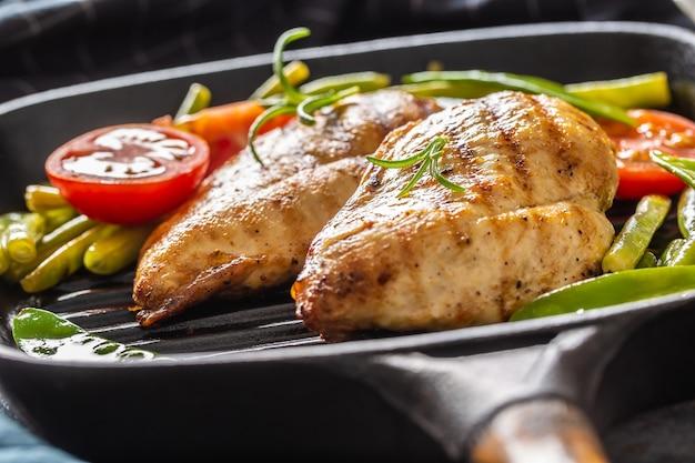 Cucina casalinga sana, pollo in padella con piselli e pomodori e rosmarino da vicino.