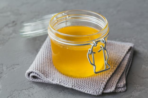 Ghee casalingo sano o burro chiarificato in un vaso su sfondo grigio cemento. un sano concetto di cibo ayurveda.