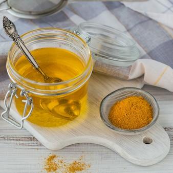Ghee casalingo sano o burro chiarificato in un barattolo e polvere di curcuma sulla tavola di legno bianca. un sano concetto di cibo ayurveda.