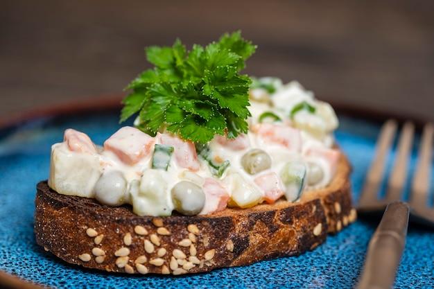 Sano panino fatto in casa con insalata di olivier nel piatto, pronto da mangiare, primo piano. cibo ucraino