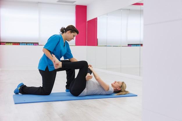 Istruttore in buona salute che allunga le gambe pazienti alla palestra