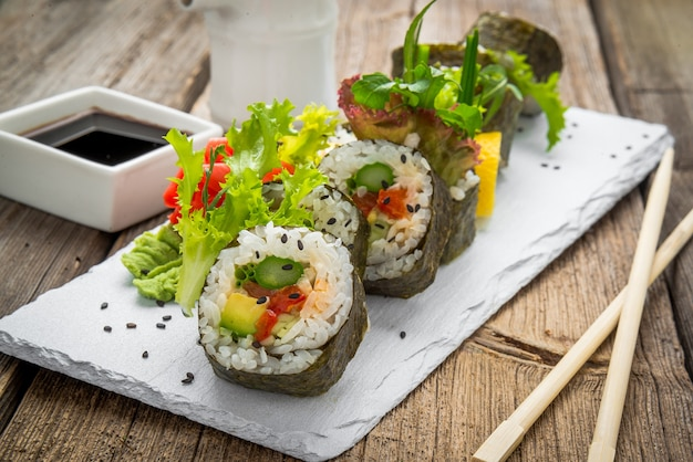 Rotolo di sushi sano di cavolo e avocado con le bacchette. panini vegetariani