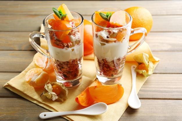 Dessert sano a strati con muesli e frutta sul tavolo