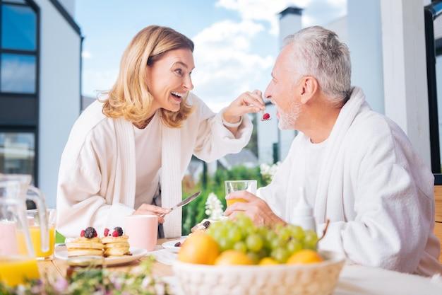 Uno stile di vita sano. belle coppie che conducono uno stile di vita sano sentendosi molto bene mentre mangiano frutta e succhi per colazione