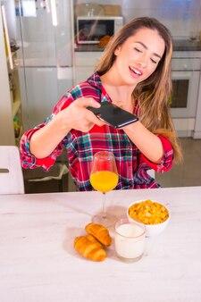 Stile di vita sano, bionda caucasica con un succo d'arancia a colazione e scattare una foto per i social network
