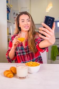Stile di vita sano, bionda caucasica con un succo d'arancia a colazione e la registrazione di un video per i social network