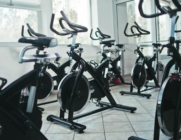 Concetto di stile di vita sano. lotto di cyclette nella classe di spinning hall vuota.