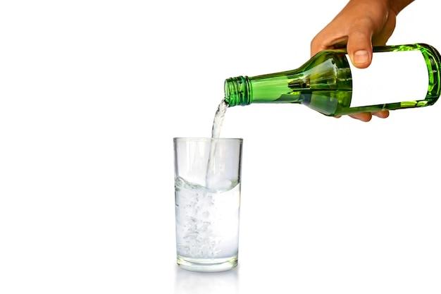 Concetto di stile di vita sano. mano della giovane signora che tiene una bottiglia per versare l'acqua di vetro separatamente su priorità bassa bianca.