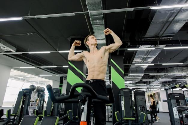 Concetto di stile di vita sano. il giovane uomo sportivo senza camicia sta esercitando la bici alla classe di filatura. allenamento cardio. giovane uomo di sport che guida bicicletta fissa nella palestra di forma fisica.