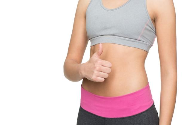 Uno stile di vita sano. ritagliata colpo di una donna con corpo in forma e tonica che mostra i pollici in su su bianco