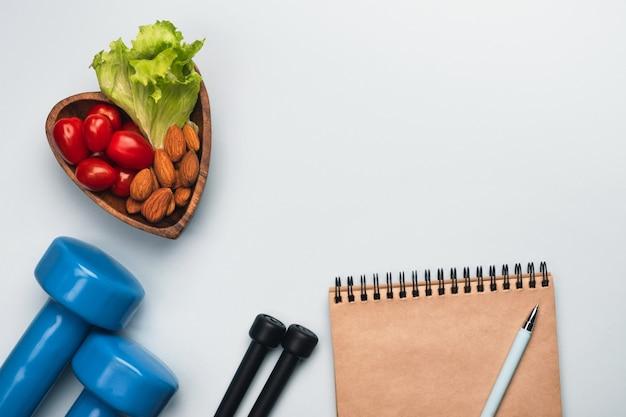 Stile di vita sano e concetto di dieta. piatto a forma di cuore con verdure e noci