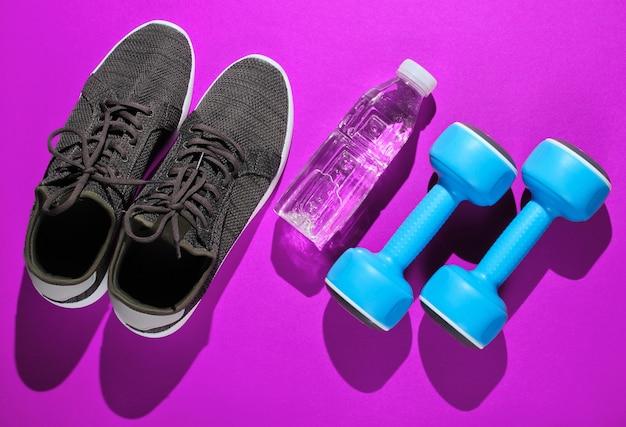 Uno stile di vita sano. manubri, bottiglia d'acqua, scarpe da ginnastica rosa