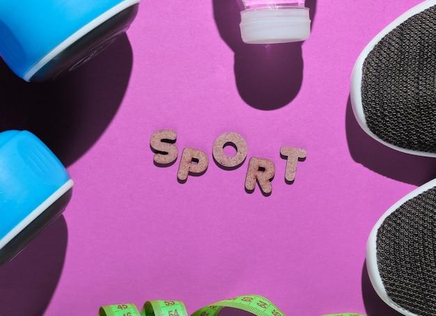 Uno stile di vita sano. manubri, righello, bottiglia d'acqua, scarpe da ginnastica rosa con parola sport