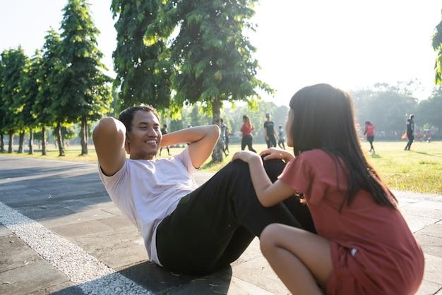 Stile di vita sano della famiglia con papà bambino seduto e bambino seduto sui piedi