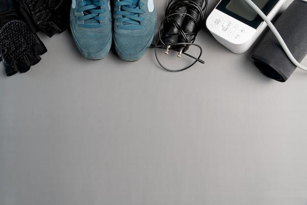 Stile di vita sano attrezzatura per la corda per saltare e sfigmomanometro su sfondo grigio