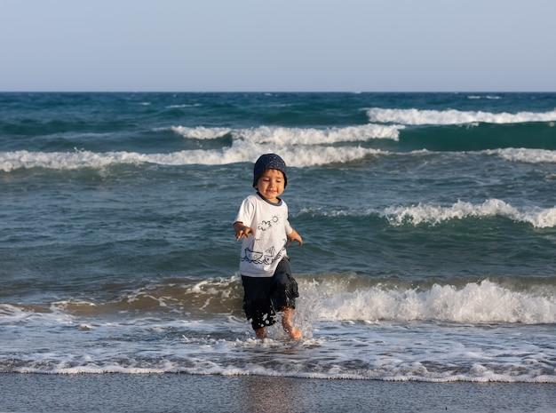Uno stile di vita sano. un ragazzino cammina e gioca in riva al mare.