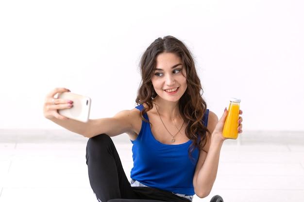 Stile di vita sano, persone e concetto di sport. donna che cattura selfie e che tiene il succo.