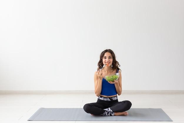 Stile di vita sano, persone e concetto di sport. donna di yoga con una ciotola di insalata di verdure.