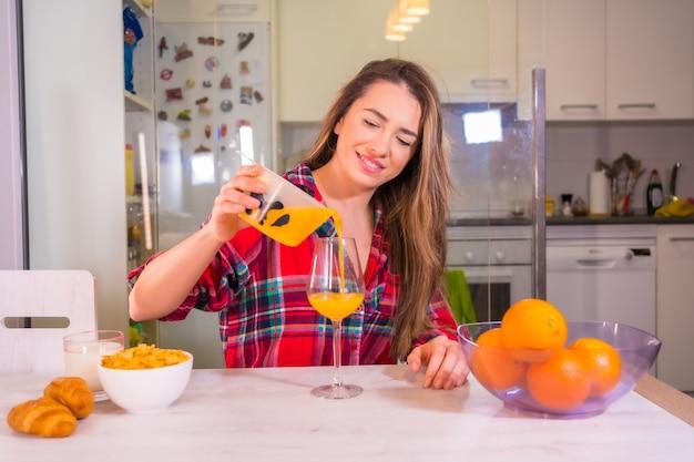 Stile di vita sano, donna caucasica abbastanza bionda in una camicia a quadri rossa che si aiuta a un succo d'arancia fresco
