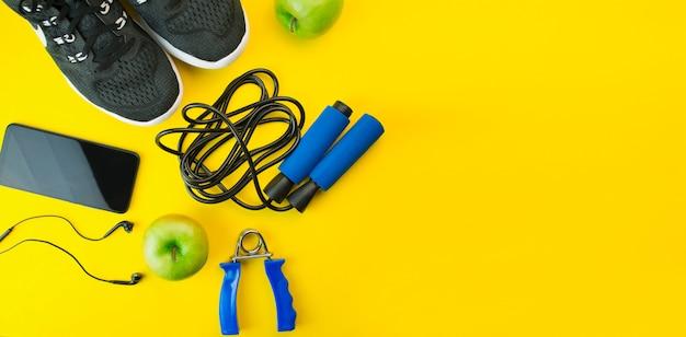 Uno stile di vita sano. attrezzature sportive su uno sfondo giallo. concetto di sport. l'appartamento stava mentendo. vista dall'alto con spazio di copia. banner.